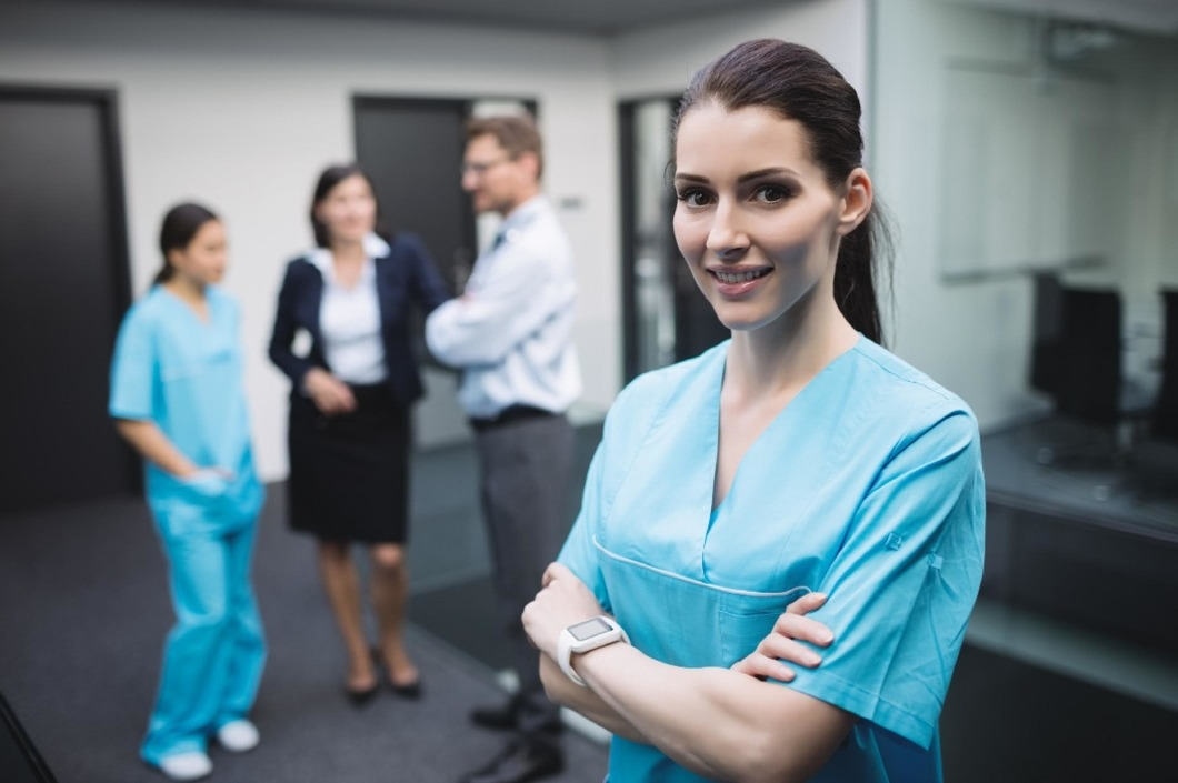 Smiling nurse in blue scrubs. Three staff are blurred in the background.